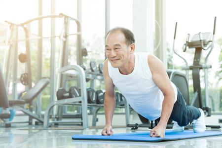 Asian senior man push up at the gym. copy space.