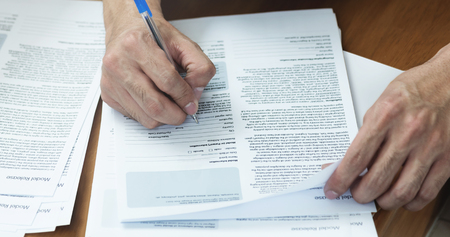 Close up of Man hand with pen writing and signing on Model release document form. Stock Photo