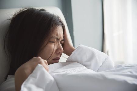 Asian woman having headache on her bed. Migraine. Illness, disease concept.