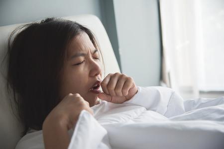 Asiatische Frau, die eine Erkältung hat. Mädchen hustet auf ihrem Bett. Krankheit, Krankheitskonzept. Standard-Bild - 77174806