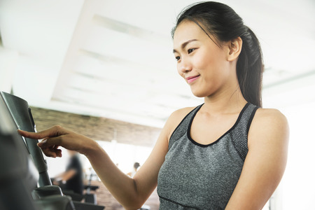 Asian woman in sportswear using treadmill at the gym.