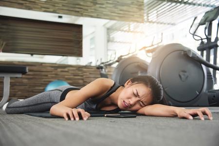Aziatische vrouw die terwijl training bij de gymnastiek flauwvallen. Stockfoto