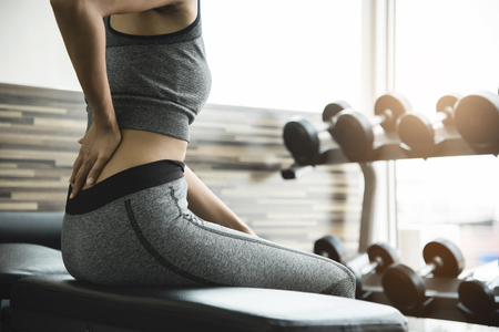 Young woman having back pain after workout at the gym. Stock Photo