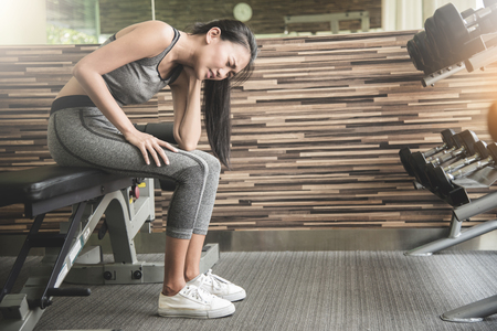 Asian woman having neck pain after workout at the gym. Stock Photo