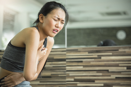 Asian woman having heart attack after workout at the gym. Stock fotó