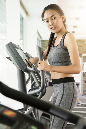 Asian woman exercising on Elliptical trainer machine at the gym. Фото со стока