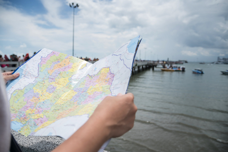 Close up woman hands holding the map at the port of the sea background.