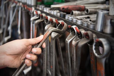 auto focus: Close up hand holding a car mechanic tool.