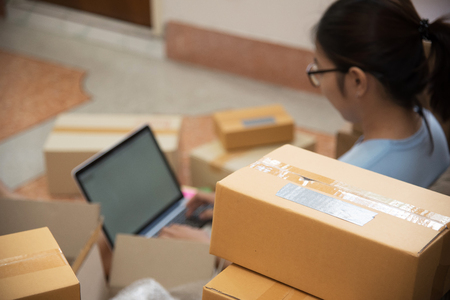 warehouse: Selective focus on box on foreground. Young Asian woman using a laptop in her small warehouse. Own business