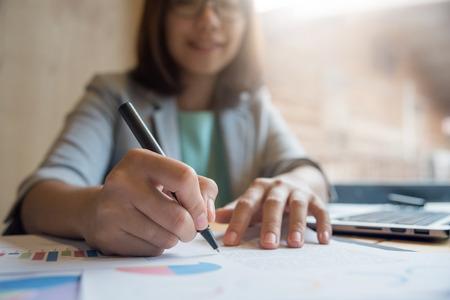 Ciérrese para arriba de la mujer de negocios asiática que trabaja con la escritura en el documento de papel con la computadora portátil.