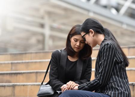 泣いていると階段の上に座って若いアジア ビジネス女性は悲しみ。解雇されました。