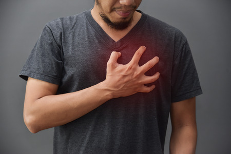 Asian beard man in gray shirt having chest pain from heart attack on grey background. Illness, exhausted, disease, tired for overtime working concept. Stock Photo