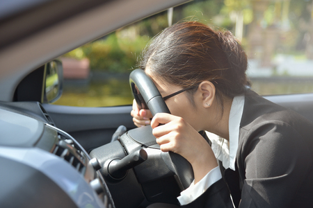 Tired Asian Business woman sleeping while driving a car. Illness, exhausted, disease, for overtime working concept.