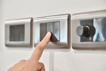 Close up hand turning on or off on grey light switches. Copy space. Archivio Fotografico