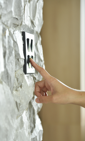 rectangle: Close up hand turning on or off on grey or black lighting switch on rough stone wall. Copy space.