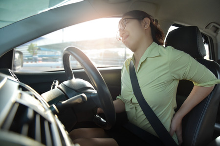 Asian glasses business woman having back pain while driving a car. Illness, disease, for overtime working concept. Archivio Fotografico
