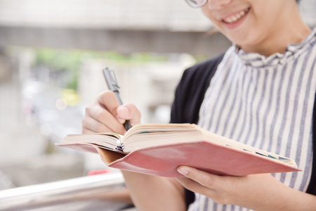 Happy Asian Business Woman writing on notebook in the city. Appointment, negotiation and reminder for business concepts. Copy space.