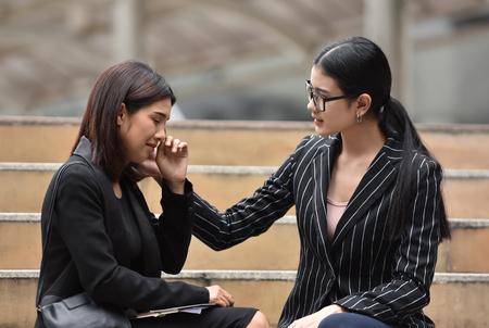 Mujer de negocios asiática joven consolando a su amigo. Tristeza Mujer llorando y sentada en la escalera. Sacked.