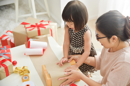 Young Mother And Her Daughter Wrapping A Gift Box For Birthday Stock Photo Picture Royalty Free Image 88793241