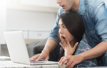 Online shopping at home. Young couple holding credit card and using laptop computer together. Stock Photo
