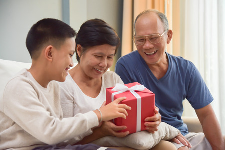 Happy Asian Family. A Boy giving a red gift box to his Grandfather and Grandmother for Birthday, Christmas and New year at their house.