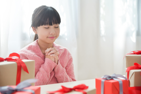 Asian girl making a wish for Birthday, Christmas and New year with gift boxes  in a white room. Copy space. Stock Photo