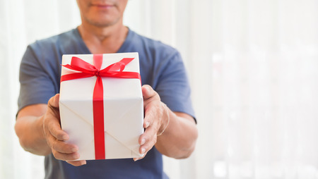 Happy Asian Elderly Man Standing And Holding A White Gift Box