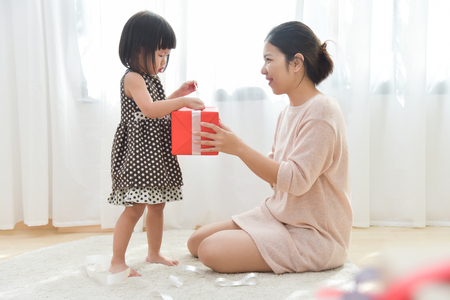 Asian Little girl and her Mother unwrapping a red gift box together in a white room for Birthday, Christmas and New year. Copy space. Happy Family celebration.