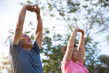 Happy Asian senior couple stretching before exercise at park outdoor.