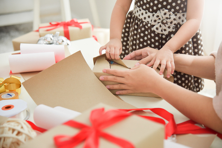 Closeup Young mother and her daughter hands wrapping a gift box for Birthday, Christmas and New year. Happy Asian family at the house. Copy space.
