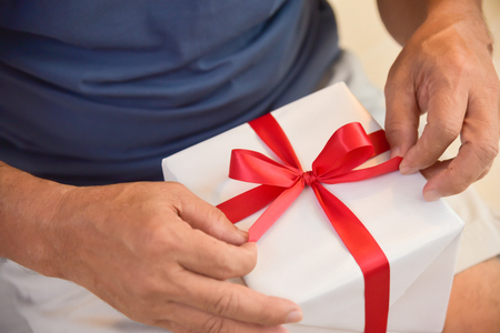 Asian Elderly Man Holding On Red Ribbon Of White Gift Box