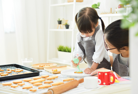 Asian Kid and young mother decorating cookies in the kitchen. Archivio Fotografico