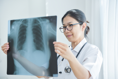 Young Asian female doctor wear glasses looking to x-ray film of patient.