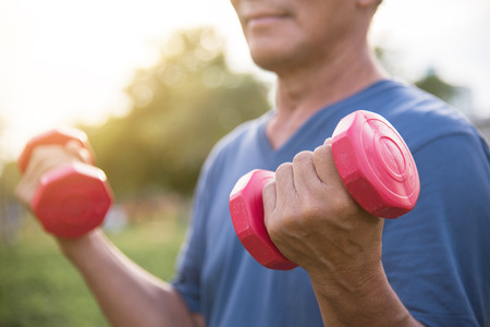 Happy Asian Senior man exercising with lifting dumbbell at park outdoor.