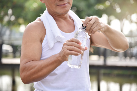 Asian senior male holding bottle of water for drinking while exercise at park outdoor background.
