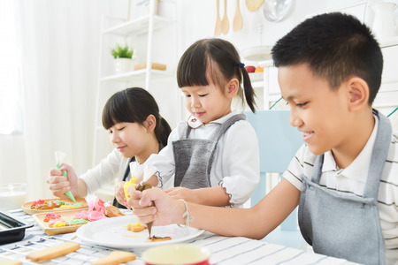Asian Kids decorating cookies in the kitchen.