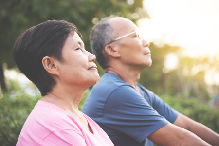 Happy Asian senior couple smiling and breathing fresh air while exercising at park outdoor. Stock Photo
