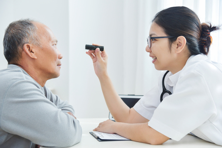 Young Asian Female Doctor wear glasses checking senior man patient eyes with flashlight in medical office. Stock Photo
