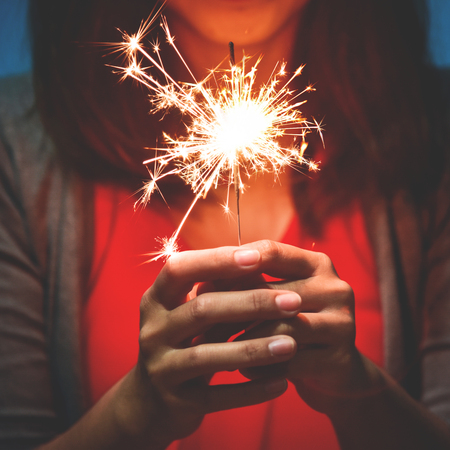 Happy Asian Woman in red shirt having fun with sparkler on blue background.