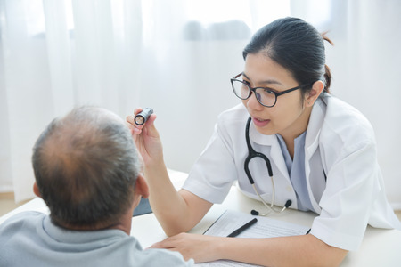 Young Asian Female Doctor wear glasses checking senior man patient eyes with flashlight in medical office. Stockfoto