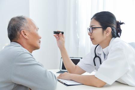 Junge asiatische Ärztinabnutzungsgläser, die geduldige Augen des älteren Mannes mit Taschenlampe im Ärztlichen Dienst überprüfen.