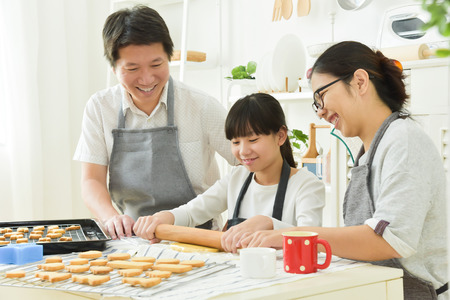 Happy Asian family baking cookies and cakes in the kitchen together.