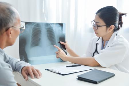 De jonge Aziatische vrouwelijke glazen die van de artsenslijtage x-ray film van Hogere mannelijke patiënt onderzoeken. Stockfoto