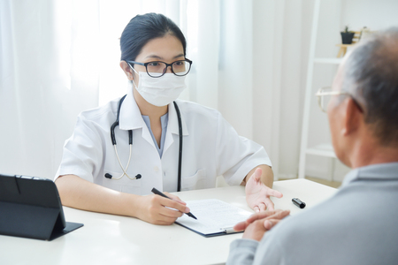 Young Asian Female Doctor with protective mask talking to senior man patient in medical office.