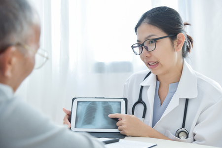 Young Asian Female Doctor wear glasses discussing with senior man patient about a chest radiograph in digital tablet computer in medical office. X-ray.