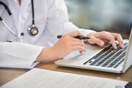 Close up on hands. Female Doctor working with laptop on wooden desk at a hospital. Medical and health care concept.  Stethoscope. Clipboard. Stock Photo