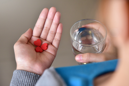 Female hands is holding red pills in heart shape and glass of water. Valentines concept. Love. Health. Disease. Illness.