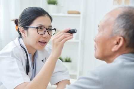 若いアジアの女性医師は、医療事務所で懐中電灯で先輩男性患者の目をチェック眼鏡を着用します。