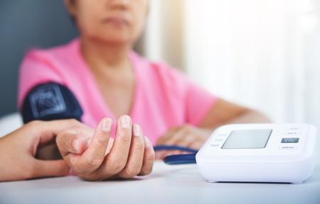 아시아 여성 의사 수석 여자 환자 펄스를 검사합니다. 건강 관리. 혈압.