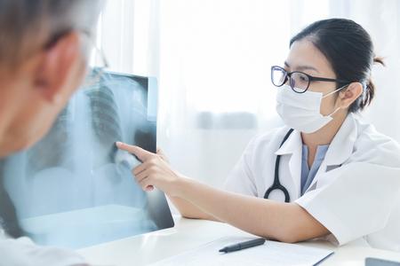 Médica feminina jovem asiática com máscara protetora examinando filme de raio-x de paciente do sexo masculino sênior.